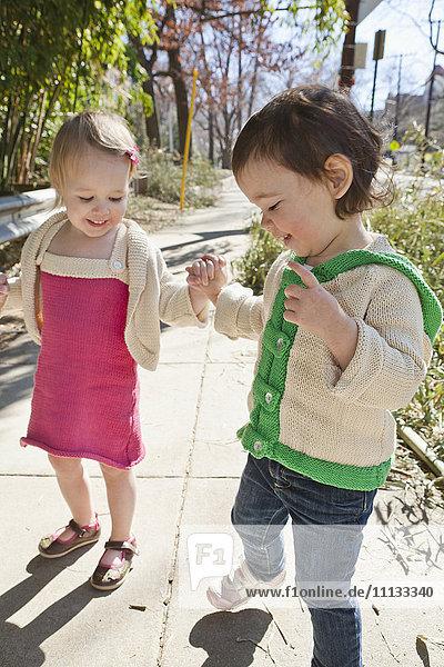 Caucasian girls holding hands on sidewalk