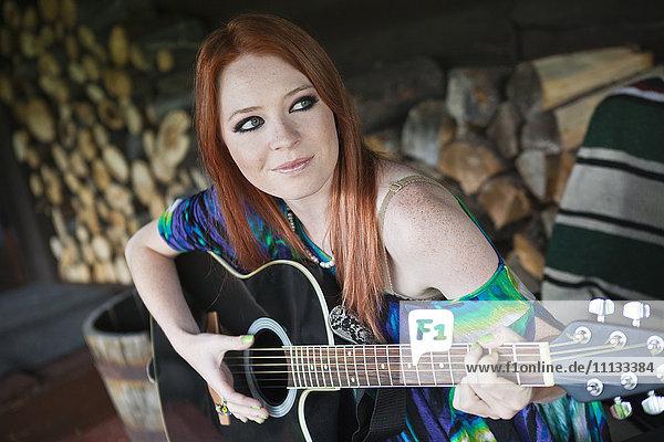 Caucasian woman playing guitar