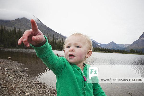 Caucasian girl standing near lake pointing