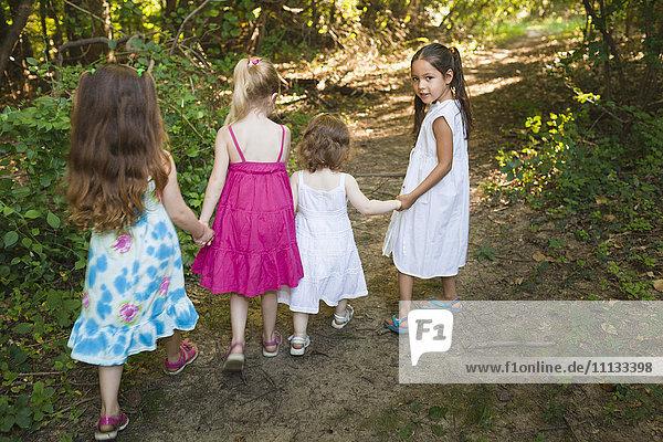 Caucasian girls walking on forest path
