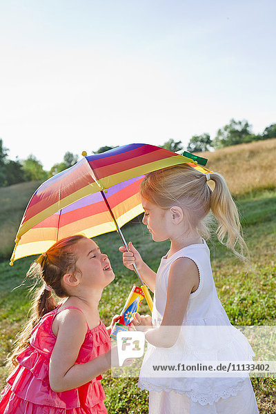 Caucasian girls in field with umbrella