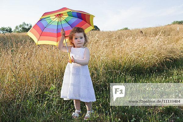 Caucasian girl in field with umbrella