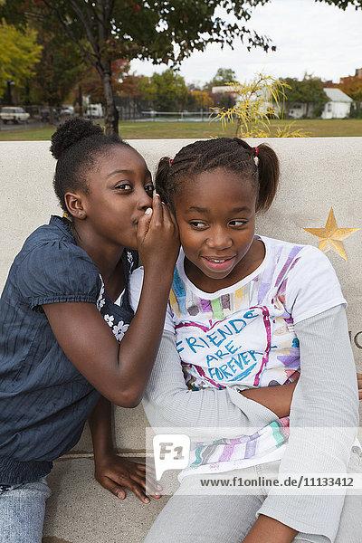 Black girls whispering together