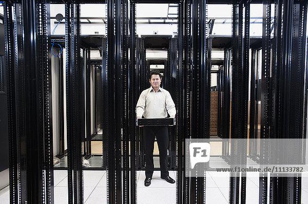 Asian businessman standing in empty server room