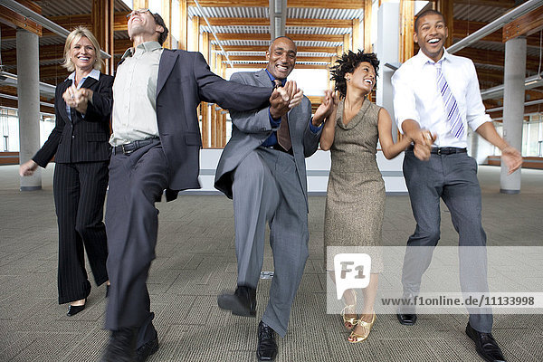 Business people dancing in empty office space