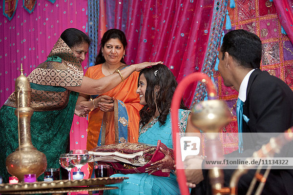 Indian woman blessing Indian bride