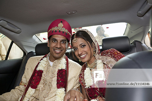 Indian bride and groom in traditional clothing in car