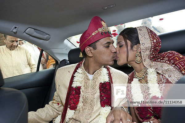Indian bride and groom in traditional clothing kissing in car