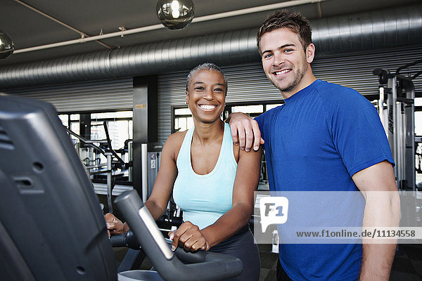 Woman with personal trainer in health club