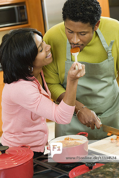 African American man tasking wife's sauce in kitchen
