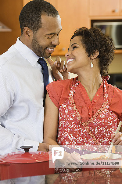 African American husband greeting wife in kitchen