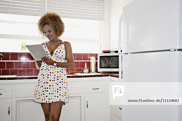 African American woman using digital tablet in kitchen