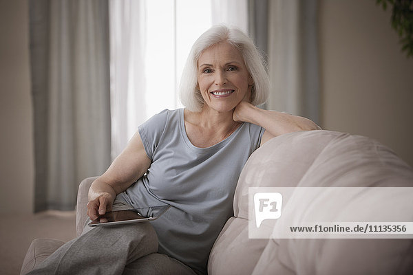 Caucasian woman sitting on sofa with digital tablet