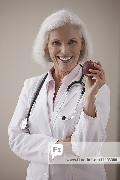 Caucasian doctor holding red apple