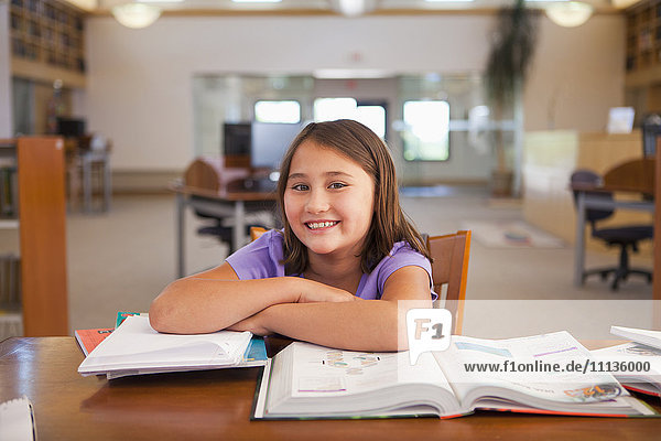 Smiling mixed race girl studying in library