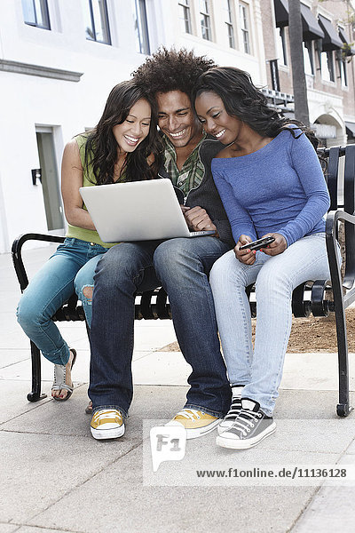 Friends sitting on bench using laptop