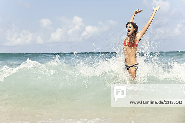 Mixed race woman enjoying ocean waves