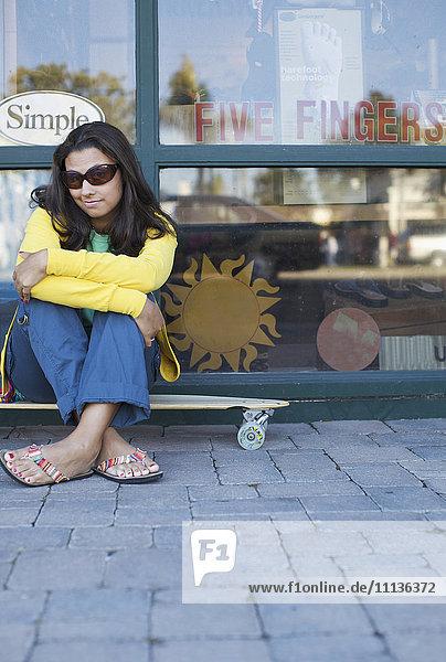 Mixed race woman sitting on skateboard