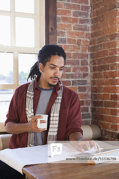 Mixed race man using digital tablet in coffee shop