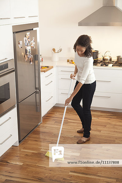 Woman sweeping kitchen