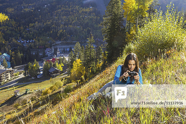 Mixed race woman taking pictures on rural hillside