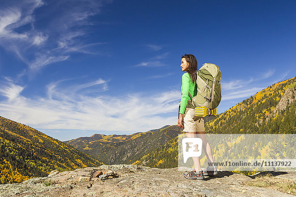 Mixed race woman standing on rocky hilltop