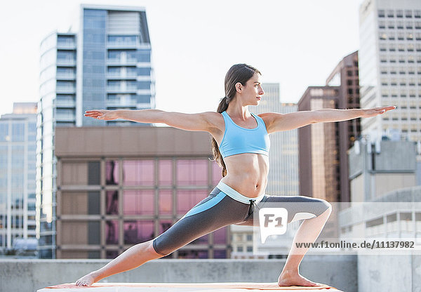 Caucasian woman practicing yoga on urban rooftop