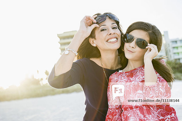 Hispanic mother and daughter wearing sunglasses