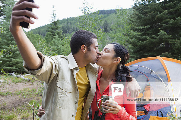 Couple camping,  kissing and taking self-portrait
