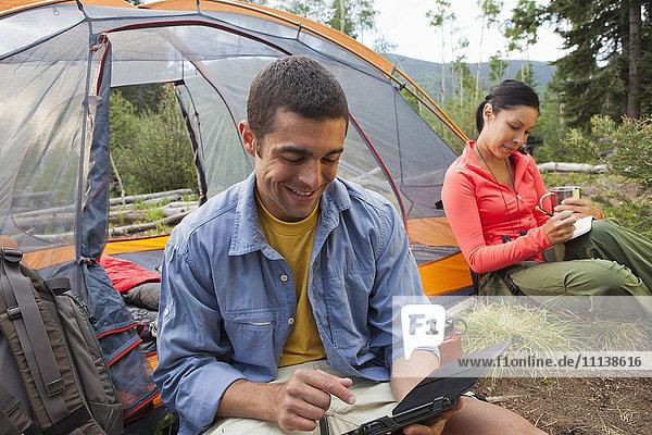 Man using digital tablet while camping