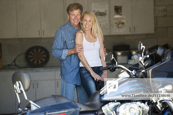 Caucasian couple with motorcycle in garage