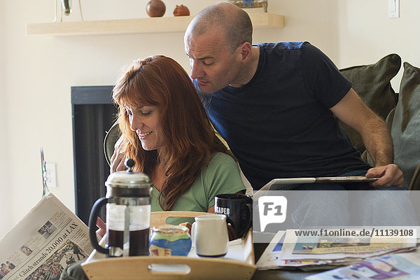 Caucasian couple reading newspaper with coffee