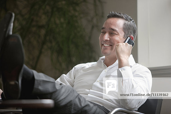 Mixed race businessman with feet on desk using cell phone