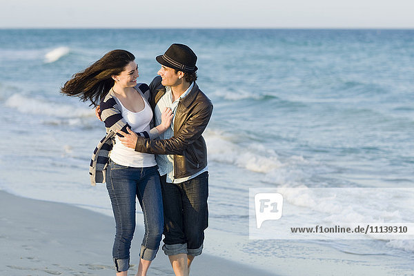 Hispanic couple walking on beach
