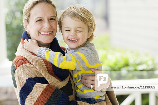 Caucasian mother holding son