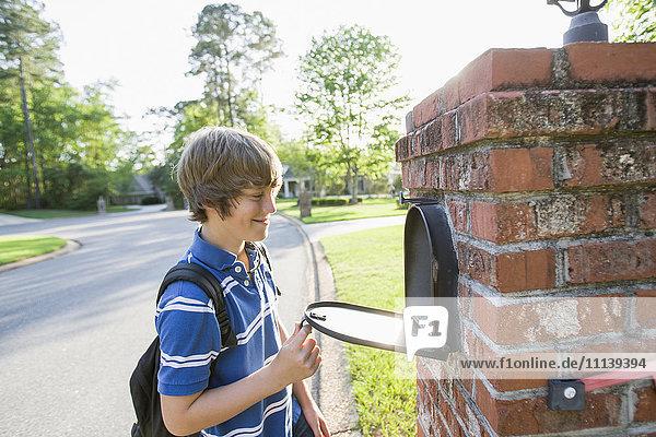 Caucasian boy opening mailbox