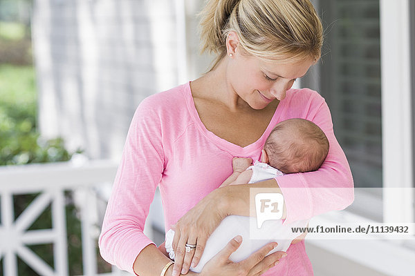 Caucasian mother holding baby on porch