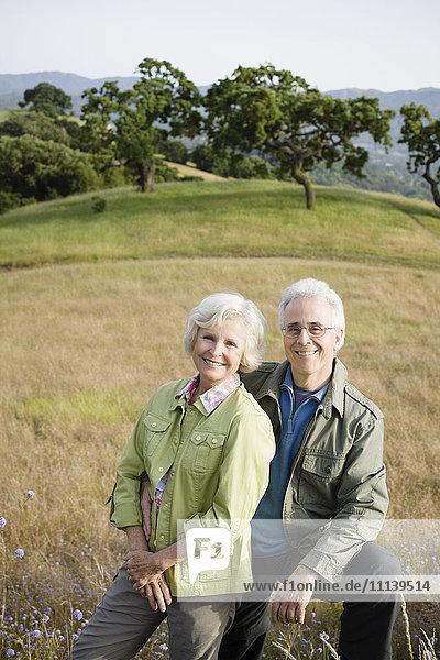 Caucasian couple standing in field
