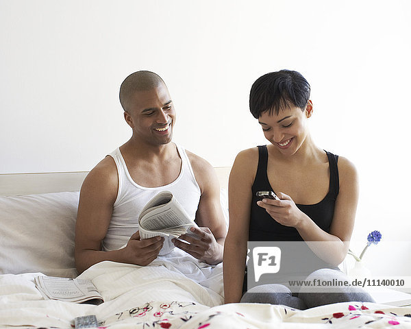 Couple relaxing in bed with newspaper and cell phone