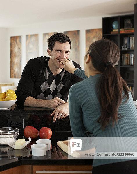 Woman feeding husband in kitchen