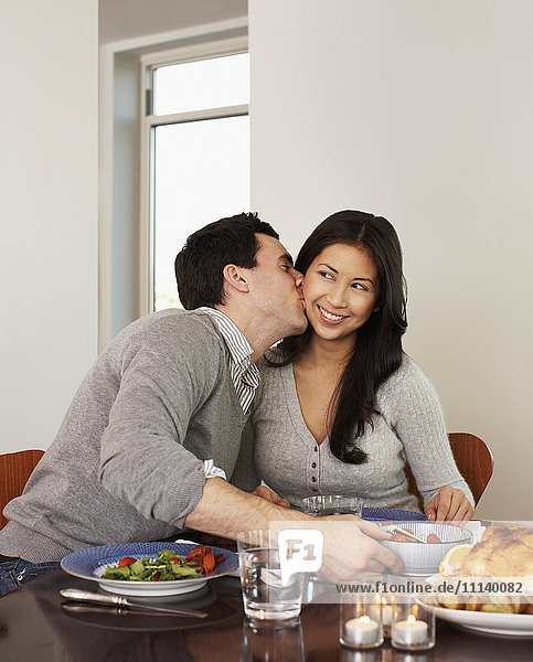 Husband kissing wife at dinner table