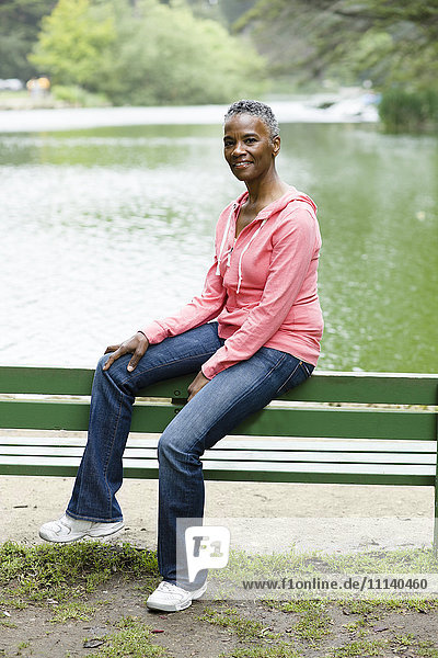 African American woman sitting on park bench near lake