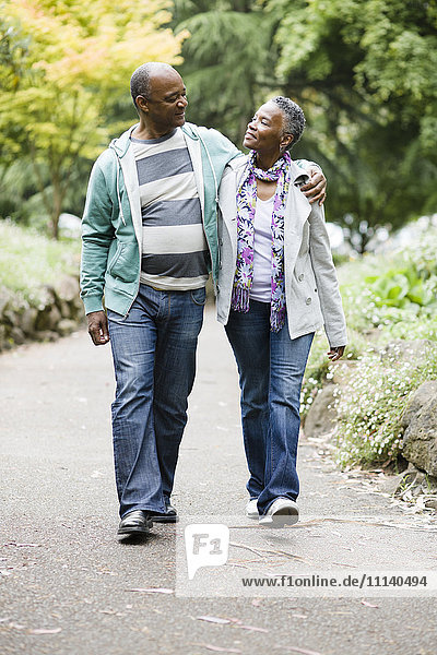 Smiling African American couple walking in park