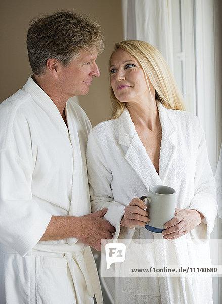 Caucasian couple having coffee in bathrobes