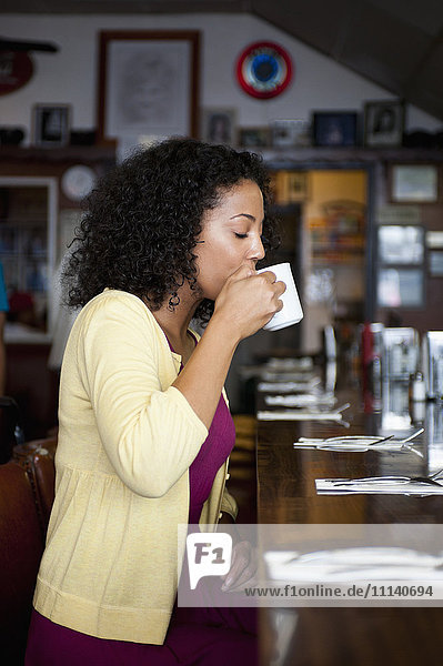 African American woman sipping coffee at diner counter
