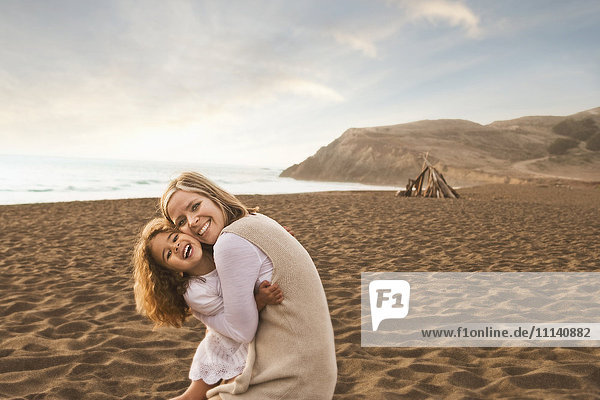 Smiling mother and daughter hugging on beach Smiling mother and daughter hugging on beach
