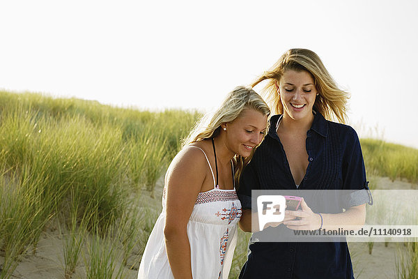 Smiling teenage girls text messaging with cell phone on beach