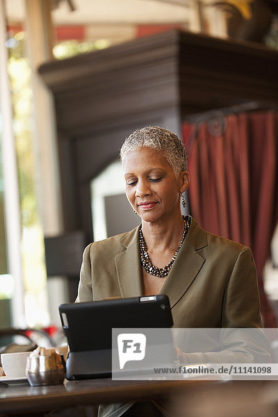 African American businesswoman using digital tablet in cafe