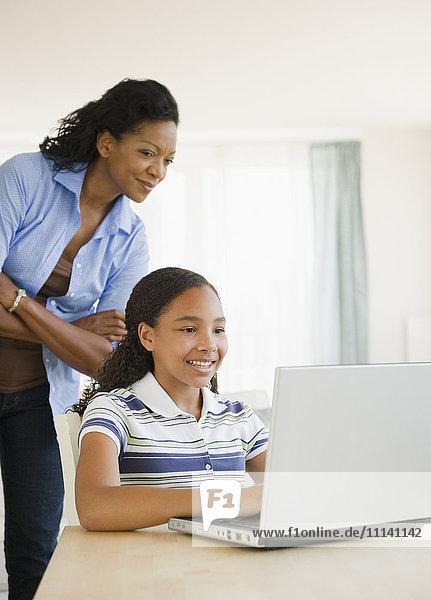 Mother watching daughter using laptop