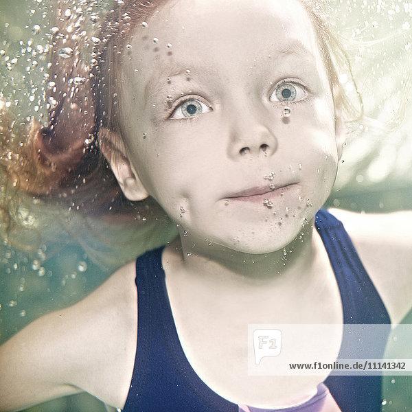 Caucasian girl swimming under water